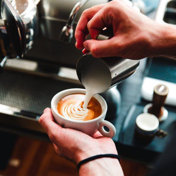 barista-pours-steamed-milk-on-espresso